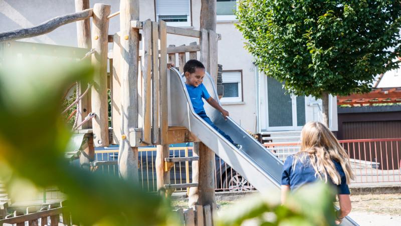 Ein Junge sitzt auf einer Rutschbahn. Neben der Rutschbahn steht eine erwachsene Frau, die zur Rutschbahn gebeugt zu dem Jungen nach oben blickt.