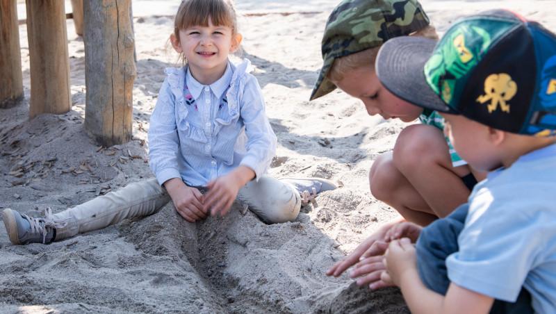 Ein Mädchen sitzt im Sandkasten und lächelt zur Kamera. Neben ihr spielen zwei Jungen im Sandkasten.