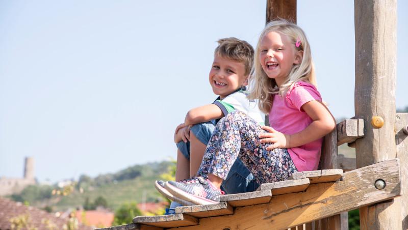Ein Junge und ein Mädchen sitzen nebeneinander auf einem hölzernen Klettergerüst. Beiden haben die Beine angewinkelt aufgestellt und blicken lächelnd in die Kamera.