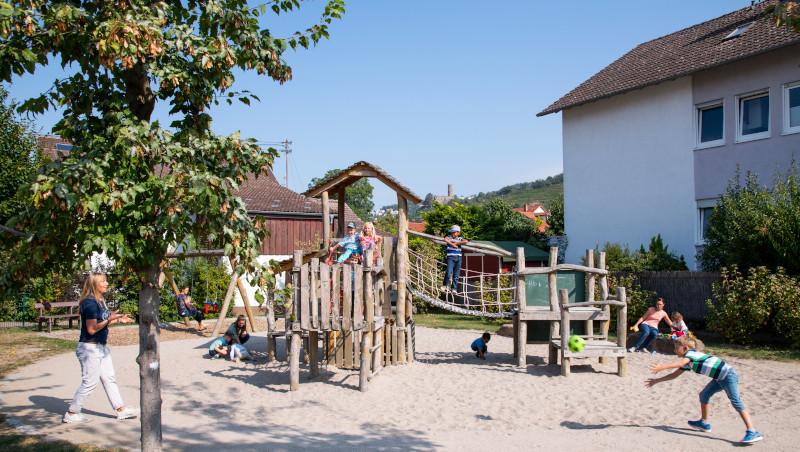 Ein Sandkasten mit einem großen Klettergerüst aus Holz in der Mitte. Auf dem Klettergerüst und im Sandkasten spielen Kinder.