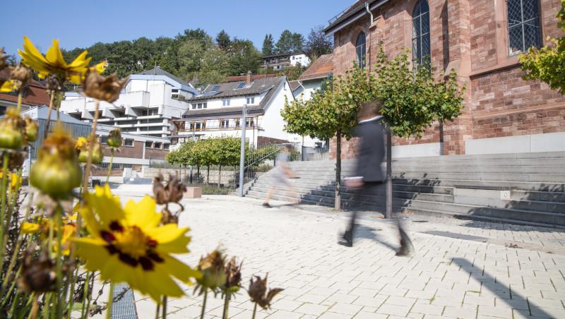Ein großer Platz mit grüner Bepflanzung und einem großen Gebäude am Bildrand. Auf dem Platz laufen zwei Personen.