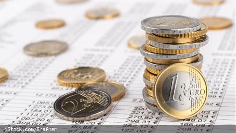 Mehrere Stapel an Euromünzen auf einem Blatt mit mehreren Tabellen