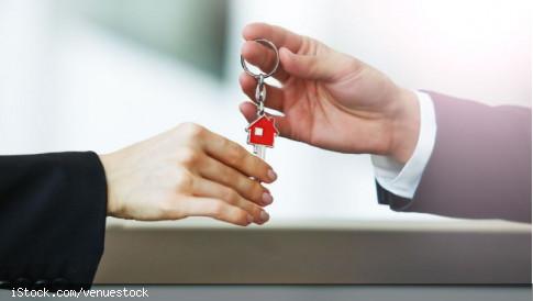 Ein Schlüssel wird übergeben (Schlüsselanhänger mit rotem Haus), es sind nur je eine Hand der beiden Personen im Anzug zu sehen