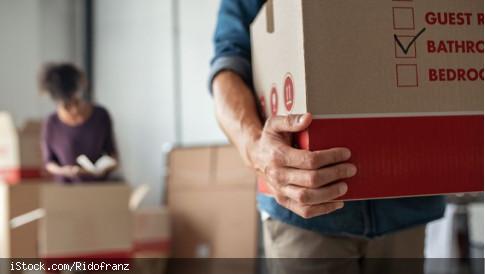 Im Vordergrund trägt eine männliche Person einen Umzugskarton aus dem Bild heraus, im Hintergrund packt eine weibliche Person einen weiteren Karton.