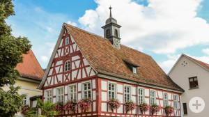 Ein altes Fachwerkhaus neben einem großen grünen Baum. Die Fenster des Hauses sind mit bunten Blumen in Blumenkästen geschmückt.