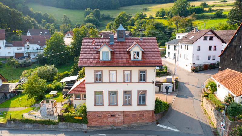 Ein großes Haus an einer steilen Straße gelegen mit einem Spielplatz daneben.