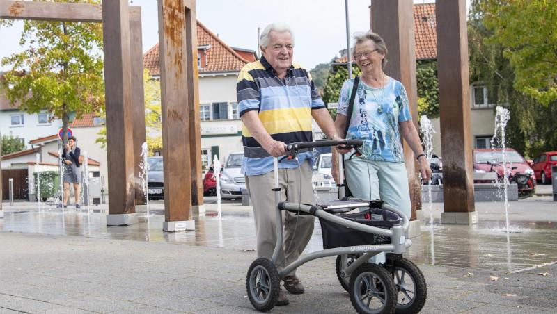 Eine ältere Dame und ein älterer Herr mit Gehhilfe beim Spaziergang durch Schriesheim.