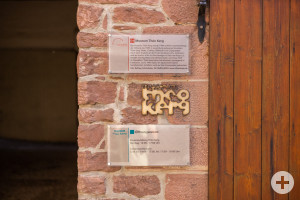 """Am Eingangsbereich des Théo Kerg Museums befinden sich zwei Informationsschilder sowie ein verschnörkelter Schriftzug """"Museum Theo Kerg""""."""