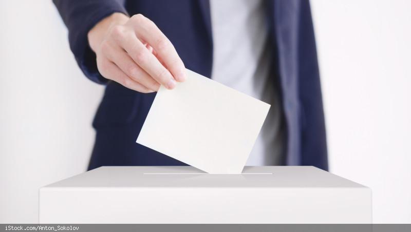 Eine Person wirft einen weißen Umschlag durch eine längliche Öffnung in einen Karton.