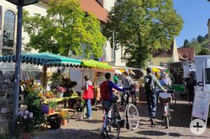 Personen laufen zwischen den Ständen des Wochenmarkts in Schriesheim